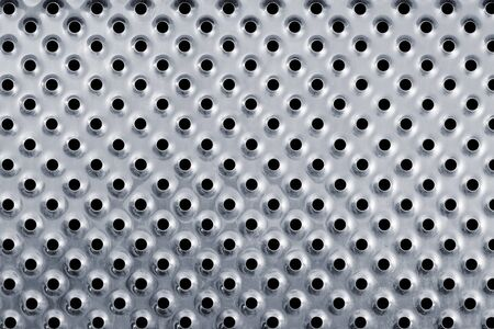 Close up of the silver colored metal background with holes.