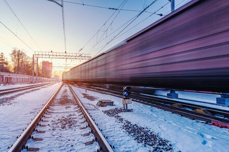 Freight train moves fast through the station at winter sunset time.