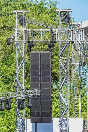 Sound system by the stage at concert time. Open air event equipment. Summer outdoor music festival preparation.
