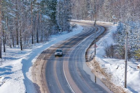 Car on the road in the winter forest.