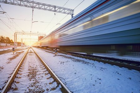 Highspeed train moves fast through the station at winter sunset time. Imagens