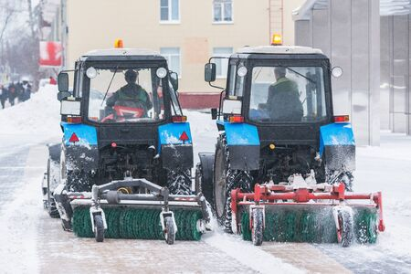 Two working snow cleaners on the street at winter time. Imagens