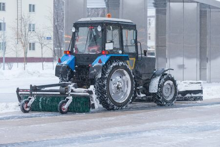 Working snow cleaner on the street at winter time.