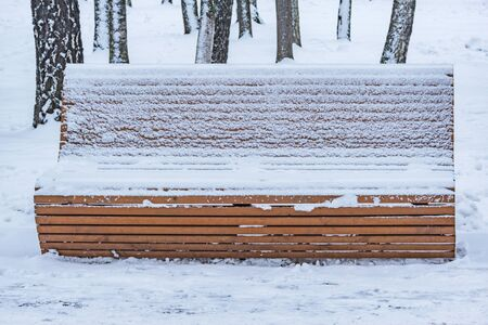 Wooden retro bench in the winter city park.