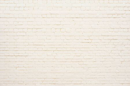 Old brick wall background painted yellow. Imagens