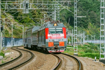 Passenger double deck train moves along the mountains. Sochi. Russia. Banco de Imagens