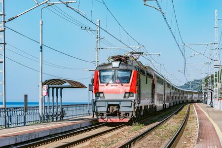 Passenger double deck train moves along the platform and Black sea shore. Sochi. Russia. Banco de Imagens