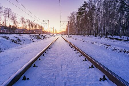 Railway track at cold winter sunset time. Imagens
