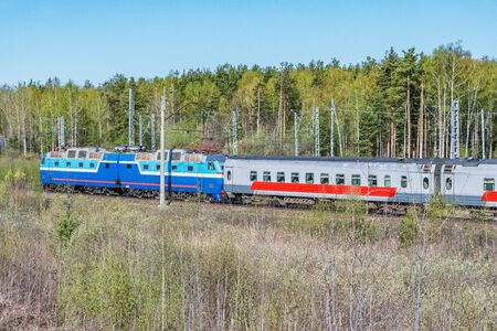 Passenger train moves on the forest background at spring day time. Imagens - 140205724