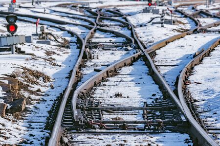 Railway tracks on the big station at winter day time.