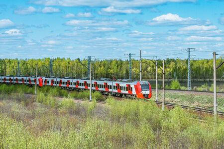 Passenger train moves on the forest background at spring day time.