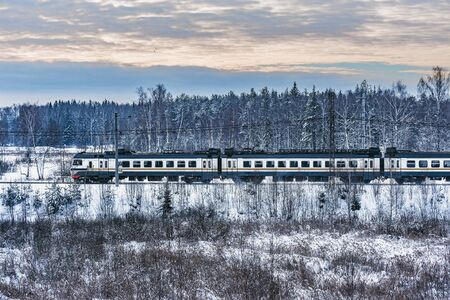 Passenger train approaches to the station on winter forest background. Imagens - 140353589