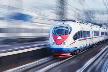 Highspeed train approaches to the station platform at winter day time. Archivio Fotografico