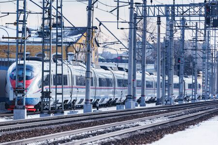 Highspeed train moves from the depot at winter day time.