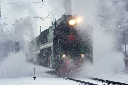 Retro steam train departs from the railway station at winter snowy time.