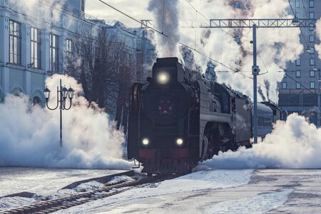 Retro steam train departs from the railway station at winter morning time. Imagens