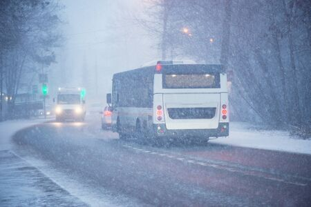 Buses move on the road at winter evening time.