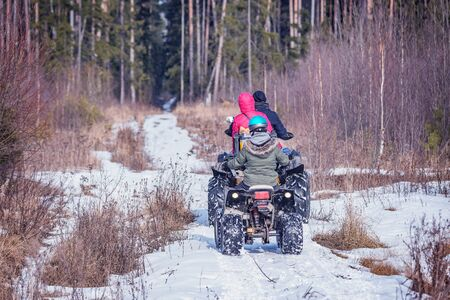 Family on the ATV Quad Bikes on the winter road. Imagens