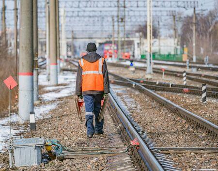 Railway worker walks on railway station territory. Archivio Fotografico