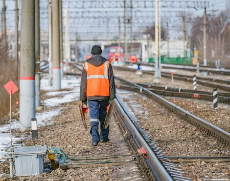 Railway worker walks on railway station territory.