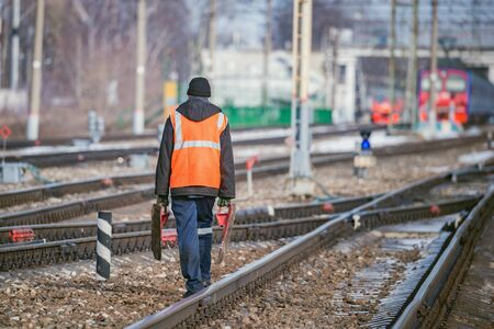Railway worker walks on railway station territory. Imagens