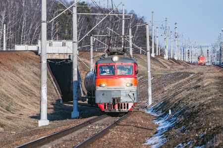 Freight train moves through the tunnel at spring day time. Stock Photo