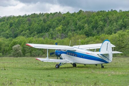 Old retro plane takes off from the small mountain airport at cloudy day time. Фото со стока