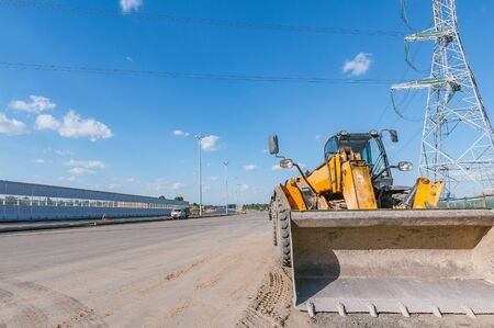 Road machine by construction site of the wide highway. Archivio Fotografico
