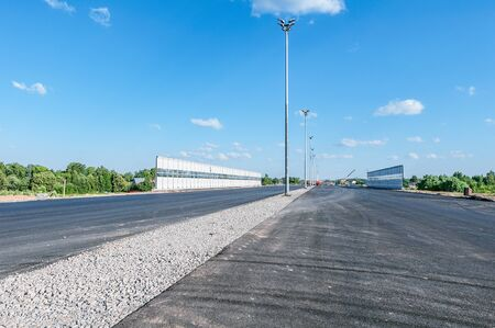 View of the new highway under construction with noise protection fence along.