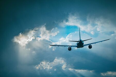 Flying of the passenger plane to the stormy clouds. Stock Photo