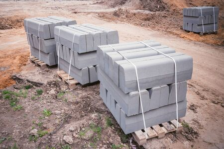 Curb stones on pallets on the construction site. Stock Photo