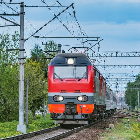 Passenger train moves from the station at evening time.. Stock Photo