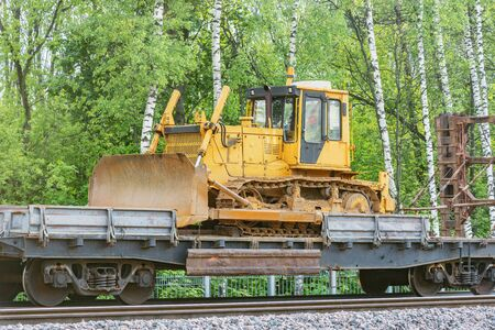 Bulldozer stands on the railway transporter by the forest.