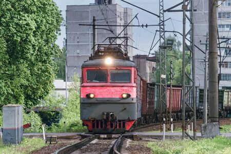 Freight train crosses the city road.