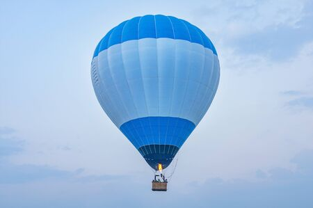 Blue hot air balloon above the land at evening time.