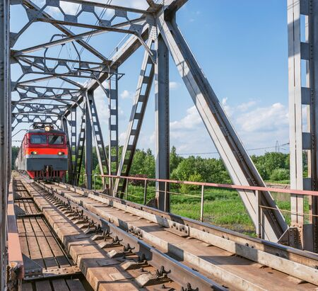 Freight train moves through the bridge above the river.