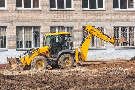 Road machine works on the construction site territory. Archivio Fotografico
