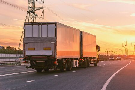 Freight truck moves on the highway at sunset time. Stock fotó