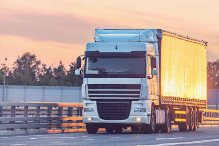 Freight truck moves on the highway at sunset time. Archivio Fotografico