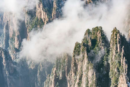 Clouds by the mountain peaks of Huangshan National park at sunrise time. China.