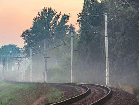Railway line at foggy summer evening.
