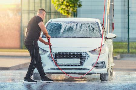Man washes his car.