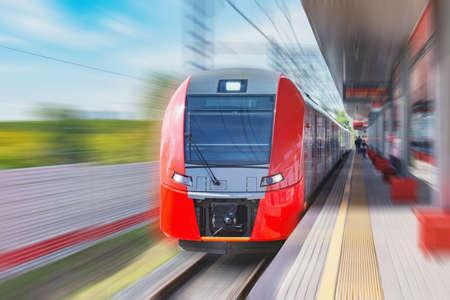 Highspeed train moves fast along the passenger platform.