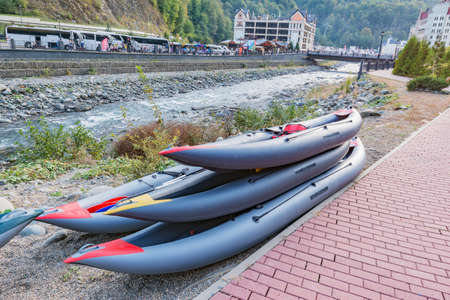 Gray inflatable boats on the mountain river shore.