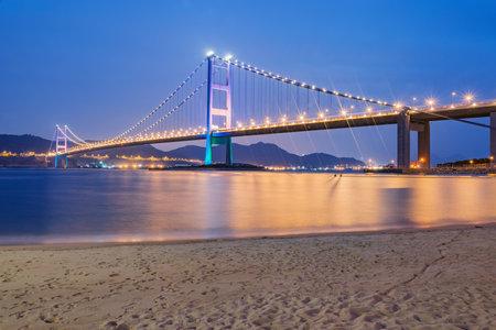 Suspension bridge to Park island at sunset. 免版税图像