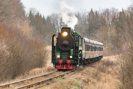 Steam train moves at autumn day time.