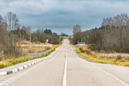 Asphalt road railway crossing on countryside background.