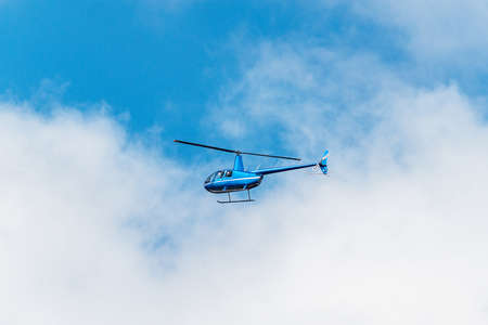 Small transport helicopter flying in the sky.