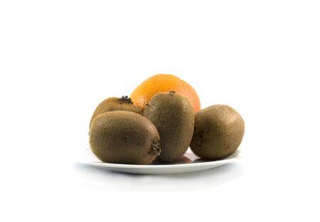 kiwis: four kiwis and orange, on a white plate