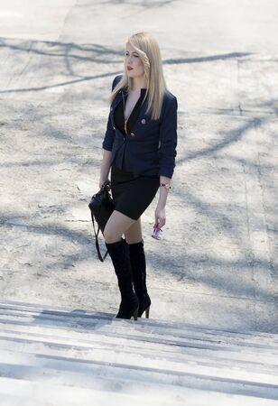 concrete steps: the stylish woman rises on concrete steps, in park